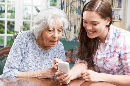 Teenage Granddaughter Showing Grandmother How To Use Mobile Phon