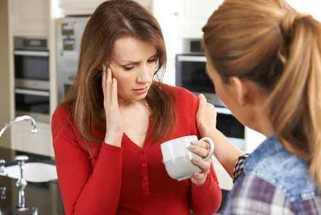 Sad Woman Being Consoled At Home By Female Friend